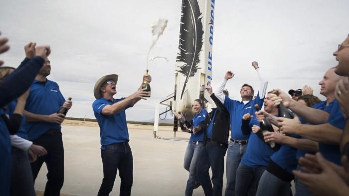 Bottle of champagne in hand and wearing a cap, Jeff Bezos celebrates the success of New Shepard's second flight. The rocket which returned to Earth is visible in the background. On the right, the person throwing their arms in the air with white sleeves is Jeff Ashby, the former NASA astronaut who now works for Blue Origin. Image credit: Blue Origin