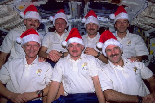 The crew of space shuttle mission STS-103 celebrates Christmas in space. Top and from left to right: the Americans Steven Smith, Michael Foale and Curtis Brown (Commander) and the Frenchman, Jean-François Clervoy. Bottom and from left to right: the Swiss Claude Nicollier and the Americans Scott Kelly and John Grunsfeld.Image credit: NASA